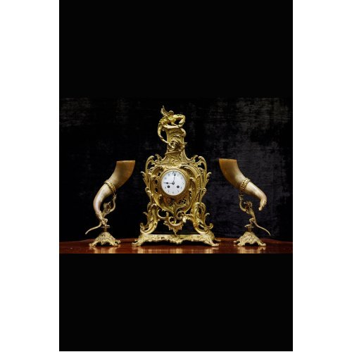 Antique clock of mantel with two animal horn vases